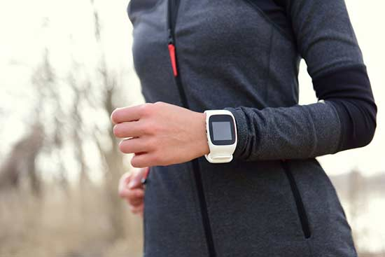 Fitness tracker on wrist of female jogger
