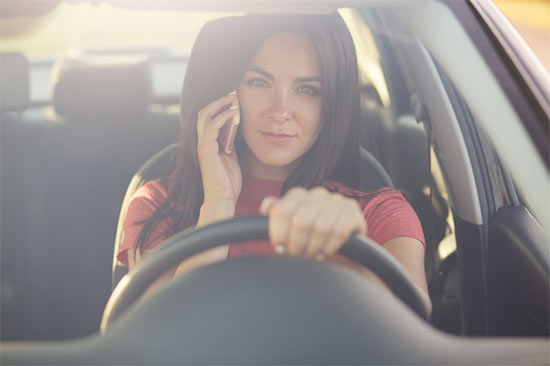 Female driver talking on cell phone while driving