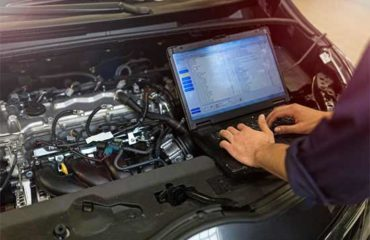 Car technician checking car data recorder