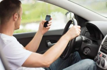 Distracted man using cell phone while driving.