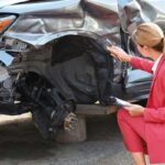 Kansas Car Wreck Settlement Adjuster Inspecting Vehicle